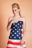 Blond woman in american flag. Young happy smiling blond woman wrapped in american flag Stock Images