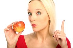 Blond woman with a apple. Young blond woman showing a apple royalty free stock image