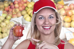 Blond woman with apple. In market Royalty Free Stock Images