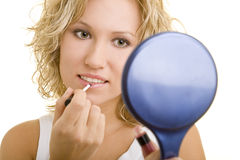 Blond woman applying makeup. Beautiful young blond woman applying lip gloss with hand mirror, white background stock photos