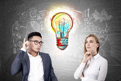 Blond woman and Asian man, light bulb. Portratif of a blond businesswoman and an Asian businessman standing near a blackboard witha a large and colorful light Royalty Free Stock Photos