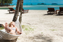 Blond woman asleep in a hammock. Royalty Free Stock Images