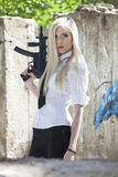 Blond woman with automatic gun. Young woman holding a automatic handgun, dressed in white blouse and tie - outdoor Stock Images