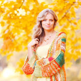 Blond woman in autumn park Stock Images