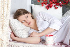 Blond woman awaking with cup of coffee at bedroom. Beautiful blond woman awaking with cup of coffee at bedroom stock photography
