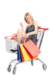 Blond woman with bags posing into a shopping cart. A blond woman with shopping bags posing into a shopping cart isolated on white background Stock Photos