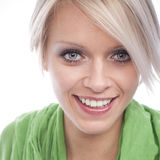 Blond woman with a beautiful smile. Green eyed blond woman with a beautiful smile and modern trendy haircut looking into the lens, headshot isolated on white Royalty Free Stock Photography