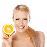 Blond woman with beautiful smile holding orange royalty free stock photo