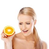Blond woman with beautiful smile holding orange Stock Images