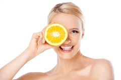 Blond woman with beautiful smile holding orange Royalty Free Stock Image