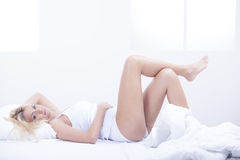 Blond woman in bed Stock Image