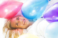 Blond woman in bed with colorful balloons Royalty Free Stock Photos