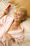 Blond woman on bed with mobile Royalty Free Stock Photo