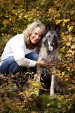 Blond woman with belgian shepherd. A portrait of a smiling blond woman with her belgian shepherd photographed in an autumnal forrest Stock Photography