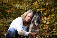 Blond woman with belgian shepherd. A portrait of a smiling blond woman with her belgian shepherd photographed in an autumnal forrest Royalty Free Stock Image