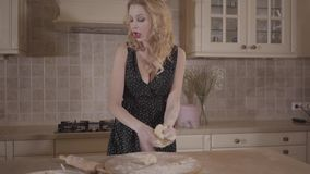 Portrait passionate blond woman with big breasts in black dress knead the dough with sigaret in mouth on the kitchen. Blond woman with big breasts in black dress stock footage