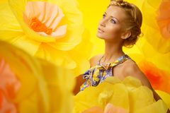 Blond woman among big yellow flowers Royalty Free Stock Images