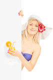 Blond woman in bikini holding a cocktail and posing behind a pan Stock Photo
