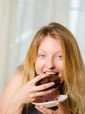 Blond woman biting a chocolate brownie Royalty Free Stock Images