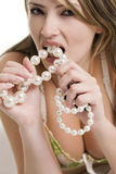 Blond woman biting a pearl necklace Stock Photography