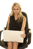 Blond woman black business dress sit with laptop serious Stock Image