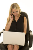 Blond woman black business dress sit laptop talk on phone Stock Photo