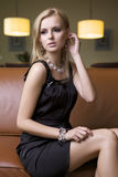 Blond woman in black dress Stock Images