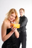 Blond woman in black dress with gift Stock Photo
