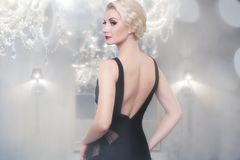 Blond woman in black dress indoors Royalty Free Stock Images