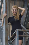 Blond woman in black dress on stairs Royalty Free Stock Photo