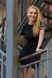 Blond woman in black dress on stairs Stock Images