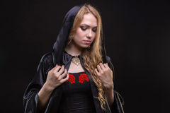 Blond woman in black hood. On black background Royalty Free Stock Photo