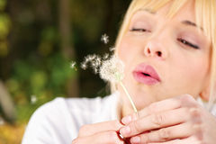 Blond woman blowing flower Royalty Free Stock Photos