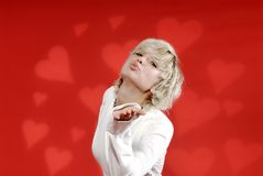 Blond Woman Blowing Kisses. Beautiful young blond woman blowing kisses against a red heart-filled background Royalty Free Stock Photo