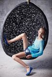 Blond woman in a blue clothes. Blond woman in a blue clothes sits in a round chair Stock Photography