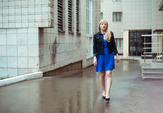 Blond woman in blue dress and denim jacket walking down the city street against background of urban architecture. Blond woman in blue dress and denim jacket Stock Image