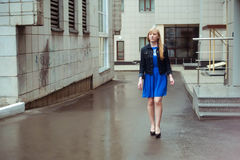 Blond woman in blue dress and denim jacket walking down the city street against background of urban architecture. Blond woman in blue dress and denim jacket Royalty Free Stock Photos