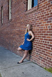 Blond Woman In Blue Dress Leaning On Brick Wall Royalty Free Stock Photo