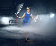 A blond woman in a blue dress posing in a studio Stock Images