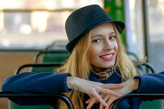 Blond woman in a blue hat sitting in the bus Royalty Free Stock Images