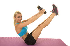 Blond woman blue sports bra sit weight legs up look Stock Photo