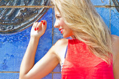 Blond woman on blue wall Stock Photo