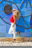 Blond woman on blue wall Royalty Free Stock Image