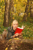 Blond woman with a book is laying on the tree Stock Photo
