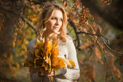 Blond woman with bouquet from maple leaves Royalty Free Stock Photos