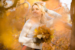 Blond woman with bouquet from maple leaves Royalty Free Stock Photo