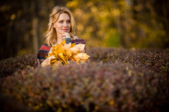 Blond woman with bouquet from maple leaves Royalty Free Stock Images