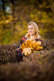 Blond woman with bouquet from maple leaves Stock Images