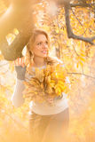 Blond woman with bouquet from maple leaves Stock Image