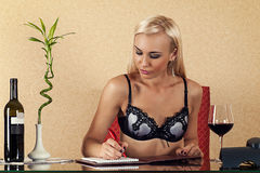 Blond woman in bra sitting at the table Royalty Free Stock Images